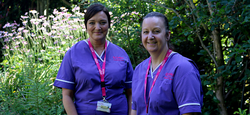 A portrait photograph of Joanne and Catherine. They stand next to each other in the St Luke's gardens and smile to the camera. They are wearing their uniforms.