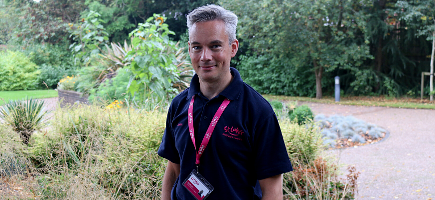 A portrait photograph of our Chaplain Mark Newitt. He smiles to the camera and stands in the St Luke's gardens. He is wearing a navy St Luke's branded polo shirt.