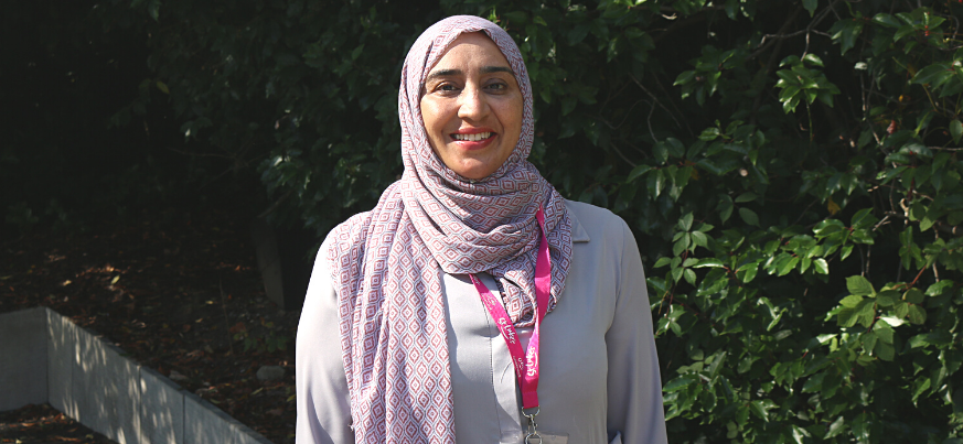 A portrait photo of Naureen Khan from Patient Services. She smiles to the camera and stands in the St Luke's gardens.
